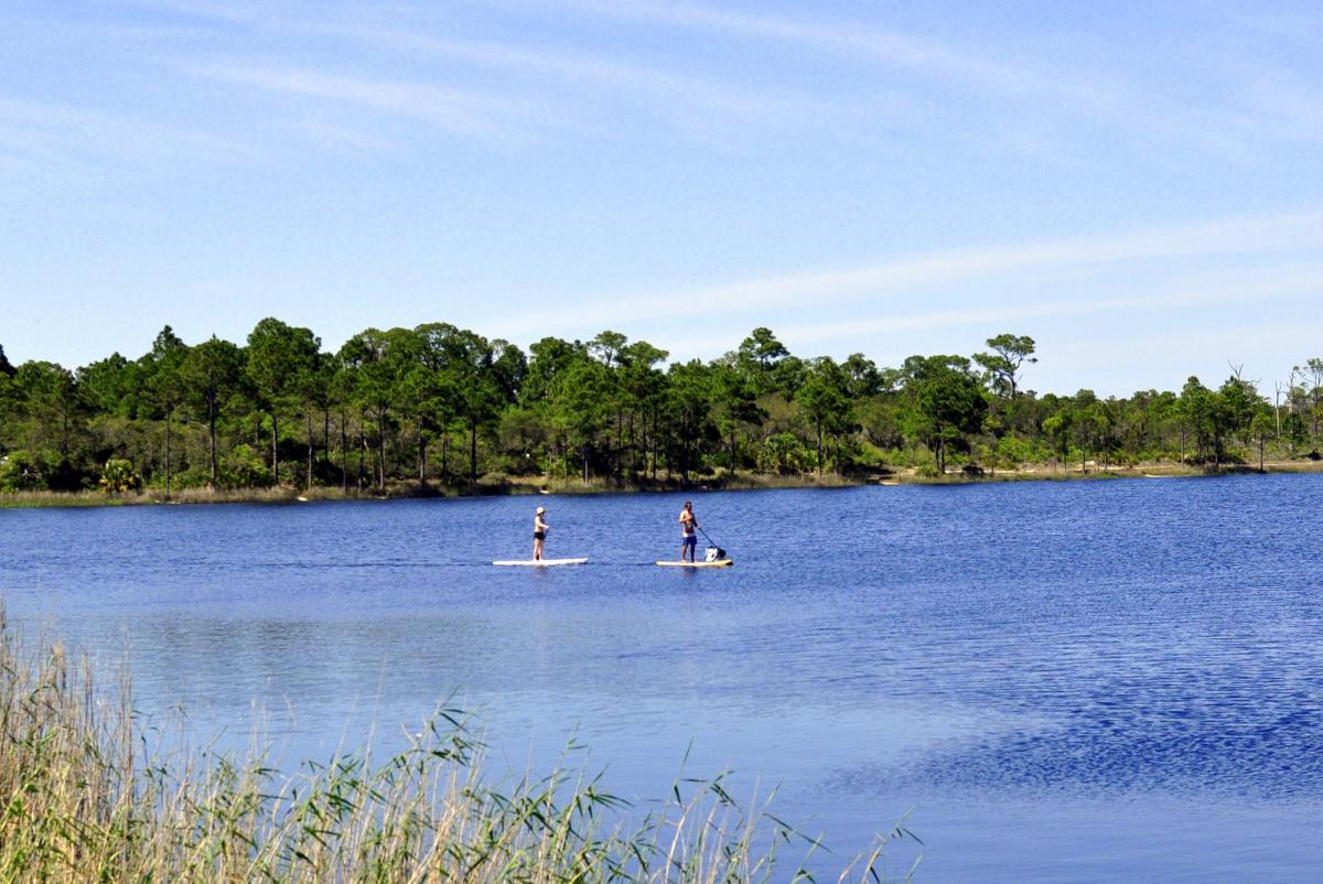 Stand-up paddleboarding on a coastal dune lake in South Walton